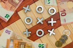 Jouant pour l'argent, la croix et le jeu zéro, euro pièces de monnaie, euro notes, Photos stock