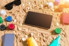 Jouant sur le concept de vacances - sable blanc avec des coquillages, des jetons de poker colorés et des cartes Vue supérieure Image libre de droits