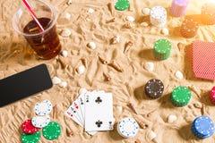 Jouant sur le concept de vacances - sable blanc avec des coquillages, des jetons de poker colorés et des cartes Vue supérieure Photographie stock