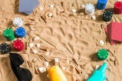 Jouant sur le concept de vacances - sable blanc avec des coquillages, des jetons de poker colorés et des cartes Vue supérieure Photos libres de droits