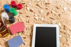 Jouant sur le concept de vacances - sable blanc avec des coquillages, des jetons de poker colorés et des cartes Vue supérieure Image stock
