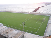 Jouer au football par la mer Images libres de droits