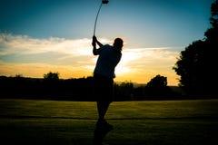 Jouer au golf dans le coucher du soleil photographie stock