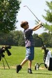Jouer au golf de garçon Photos stock