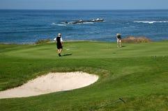 Jouer au golf par la mer Image libre de droits