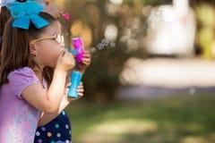 Jouer avec des bulles à un parc Images libres de droits