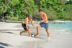 Jouer d'amis footbal à la plage tropicale ensoleillée Photos stock