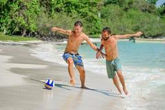 Jouer d'amis footbal à la plage tropicale ensoleillée Photographie stock