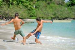 Jouer d'amis footbal à la plage tropicale ensoleillée Image libre de droits
