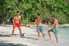 Jouer d'amis footbal à la plage tropicale ensoleillée Photo libre de droits