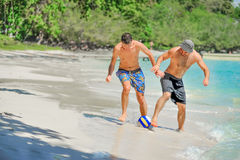 Jouer d'amis footbal à la plage tropicale ensoleillée Photo stock