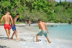 Jouer d'amis footbal à la plage tropicale ensoleillée Photographie stock libre de droits