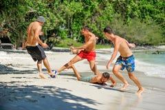 Jouer d'amis footbal à la plage tropicale ensoleillée Image stock