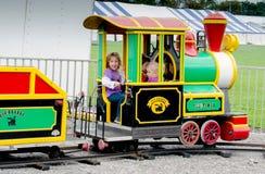 Jouer dans un petit train à un festival extérieur Photographie stock