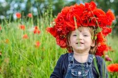 Jouer de bébé de petite fille heureux sur le champ de pavot avec une guirlande, un bouquet des pavots rouges de la couleur A et l Image libre de droits