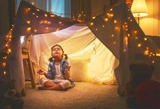 Jouer de fille d'enfant médite dans la pose de yoga dans la tente à la maison photographie stock libre de droits