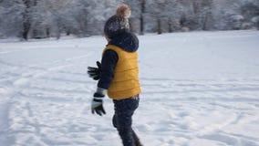 Jouer de garçon extérieur en parc d'hiver banque de vidéos