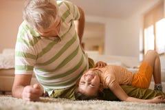 Jouer de grand-papa et de petite-fille Amusement sur le plancher Image libre de droits