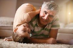 Jouer de grand-papa et de petite-fille Amusement sur le plancher Photographie stock libre de droits