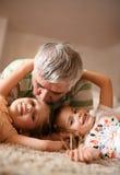 Jouer de grand-papa et de petite-filles Image stock