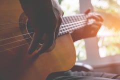 Jouer de guitariste de guitare acoustique Instrument de musique avec le perfo Images stock