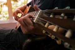 Jouer de guitariste de guitare acoustique Instrument de musique avec le perfo Photo stock