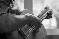 Jouer de guitariste de guitare acoustique Instrument de musique avec le perfo Photos stock