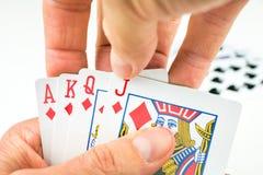 Jouer des cartes dans le tisonnier Ouvrez les dernières cartes davantage - soyez une quinte royale Images libres de droits