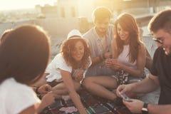 Jouer des cartes sur un dessus de toit de bâtiment Photos stock