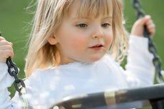 Jouer extérieur de sourire heureux de jeune de bébé vraie de personnes fin blonde caucasienne de fille sur l'oscillation Photographie stock