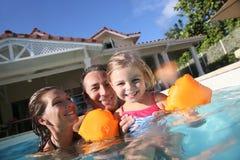 Jouer familly heureux dans la piscine Image stock