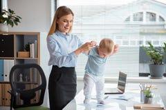 Jouer femelle sortant avec l'enfant sur le lieu de travail Photographie stock libre de droits