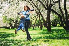 Jouer heureux de fils de mère et d'enfant en bas âge extérieur au printemps ou parc d'été Image stock