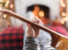 Jouer la guitare par le coin du feu Image stock