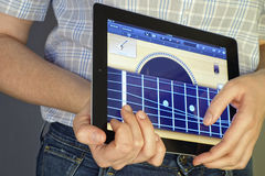 Jouer la guitare sur Ipad Photo stock
