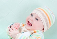 Jouer le bébé sur une couverture verte dans un commutateur tricoté Images stock