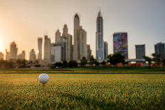 Jouer le golf au coucher du soleil La boule de golf est sur la pièce en t pour une boule de golf Photo libre de droits