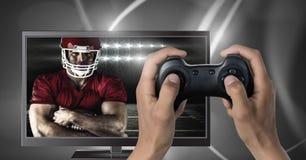 Jouer le jeu d'ordinateur de football américain avec le contrôleur dans des mains photographie stock libre de droits