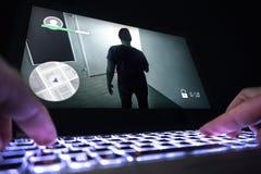 Jouer le jeu vidéo avec l'ordinateur portable Ordinateur et jeu en ligne Photo stock