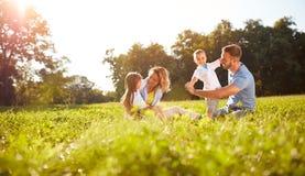 Jouer masculin et femelle avec des enfants dehors Image libre de droits