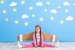 Jouer pilote de fille avec le paquet de jet de jouet à la maison Succès et concept de chef Image stock