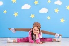 Jouer pilote de fille avec le paquet de jet de jouet à la maison Succès et concept de chef Image libre de droits