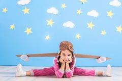 Jouer pilote de fille avec le paquet de jet de jouet à la maison Succès et concept de chef Photographie stock