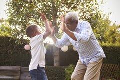 Jouer première génération noir avec son petit-fils dans un jardin Image libre de droits