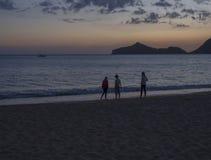 Jouer trois childern sur la plage d'Agios Georgios Pagon de bord de mer à l'île de Corfou, Grèce à l'heure bleue après coucher du image stock