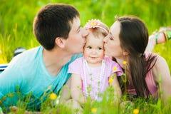 Joues de baiser de maman et de papa de petite fille Photo stock