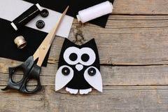 Jouet bourré de hibou de feutre, feuilles noires et blanches de feutre, ciseaux, fils, boutons sur un fond en bois de vintage ave Photo stock