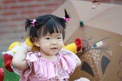 Jouet chinois mignon de peluche de jeu de bébé sur la pelouse Images stock