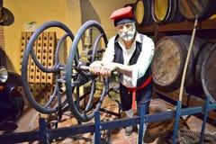 Jouet dépeignant un vieux vin-fabricant se tenant à côté des barils image stock