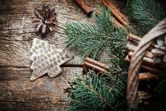 Jouet d'arbre de sapin en métal de Noël de vintage, cônes de pin, cannelle, branches de conifére sur le Tableau en bois Images stock